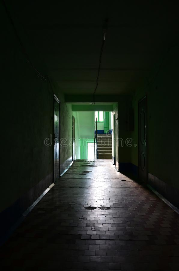 The gloomy corridor of a neglected public building. Public space in a poor residential high-rise buildin. G royalty free stock images