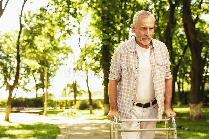 A gloomy old man walks through the park with stilts for adults stock photo