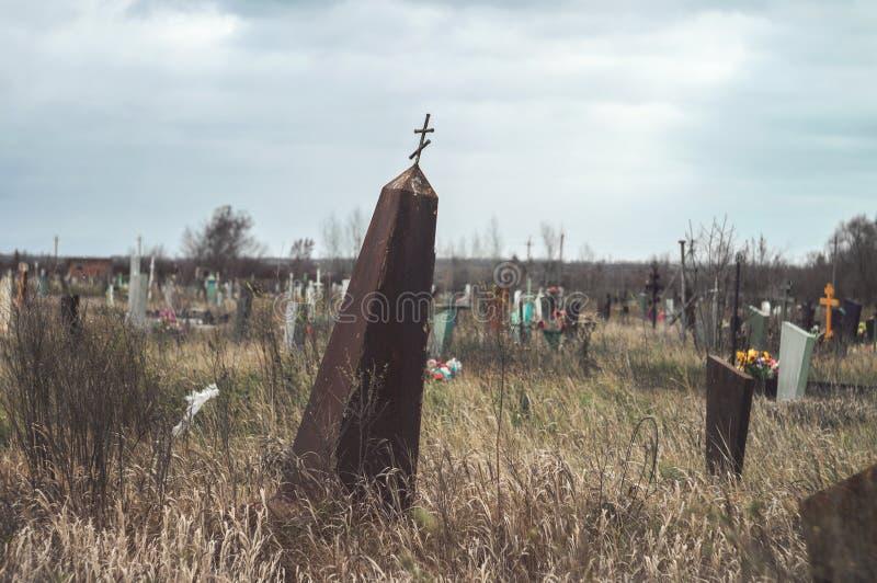 Gloomy rickety verlaten obelisk gravestone met een kruis op een begraafplaats op een bewolkte herfstdag Oude graf vergeten stock afbeelding