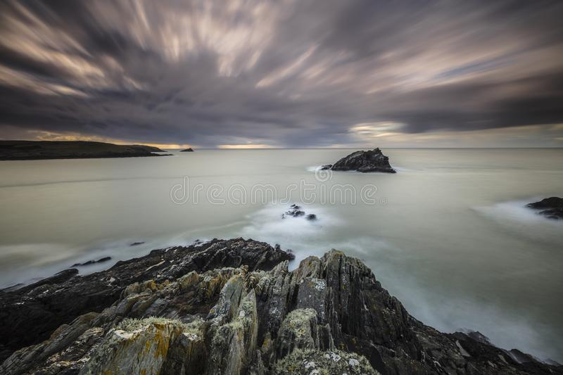 Gloomy scenery of the calm ocean under the dark sky  in Pentire Point East, Cornwall, UK. A gloomy scenery of the calm ocean under the dark sky looking like it royalty free stock images