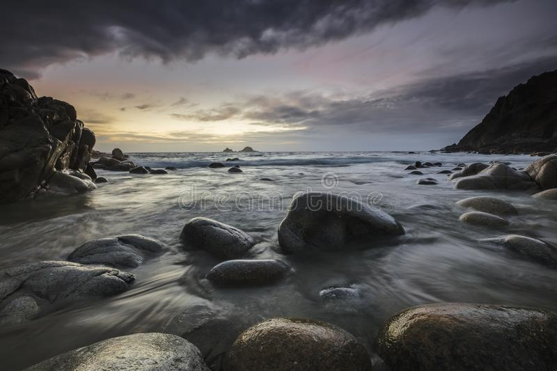Gloomy scenery of the ocean becoming calmer after the rain in Nr. Lands End, Cornwall, UK. A gloomy scenery of the ocean becoming calmer after the rain in Nr stock image