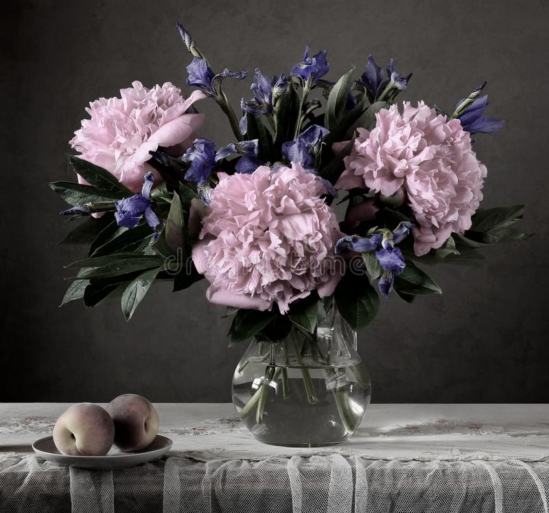 Gloomy still life with flowers and fruit in a dark key. royalty free stock image