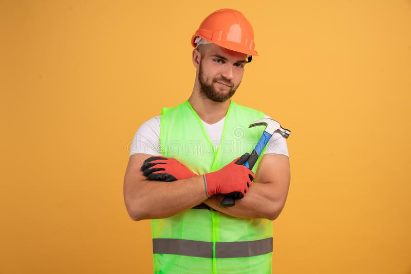 Gloomy unhappy male repairer has sad tired look, keeps hands crossed, holds hammer in hand, fatigue after repairing and manual. Work, wears special uniform stock image