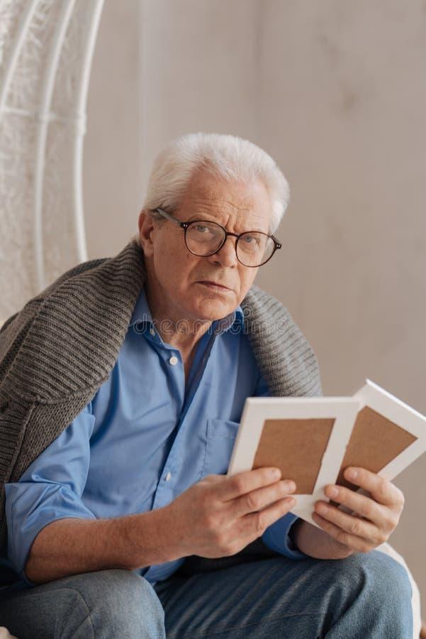 Gloomy unhappy man having old photos in his hands. Precious moments. Gloomy unhappy elderly man sitting and having old photos and his hands while being nostalgic stock image