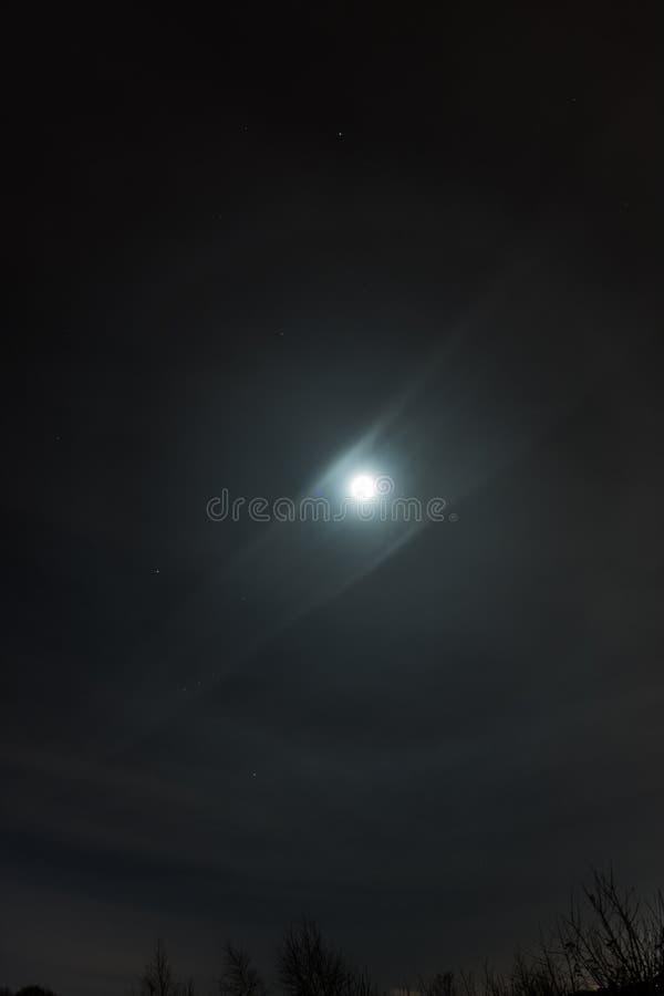 Gloria 22 runt om fullmånen i vinterhimlen med moln fotografering för bildbyråer