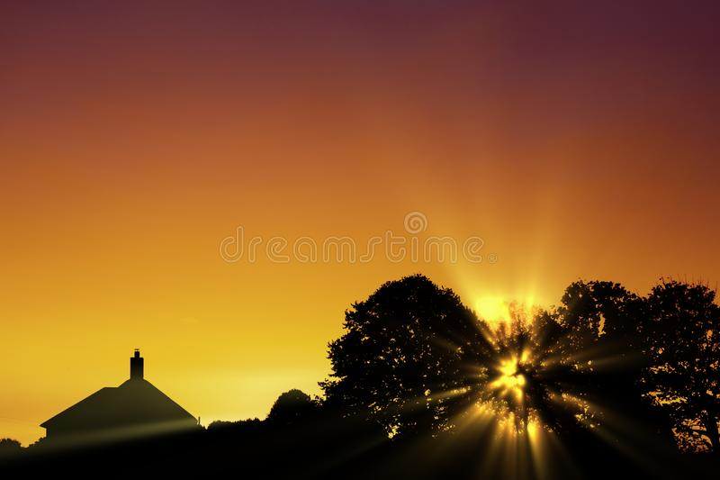 Glorious sunrise over silhouette skyline. Glorious golden sunrise through the trees with a house roof in silhouette. Graduated orange skyline about the horizon stock photography