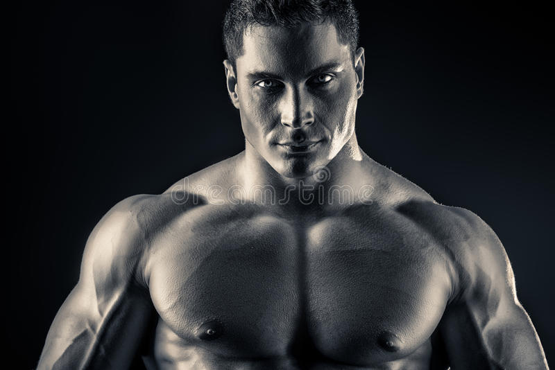 For glory. Handsome muscular bodybuilder posing over dark background. Glory of the champion royalty free stock photo
