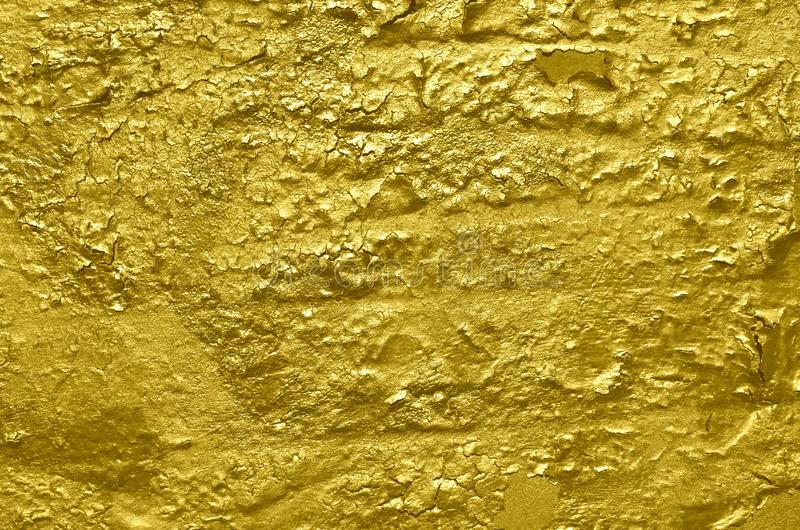 Glossy cracked peeling paint on wall of golden color royalty free stock photos