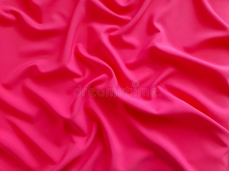 Glossy Texture, flat coral background, fabric pattern. Vivid and rich coral fabric, heavy fabric on a white background, wallpaper royalty free stock photo