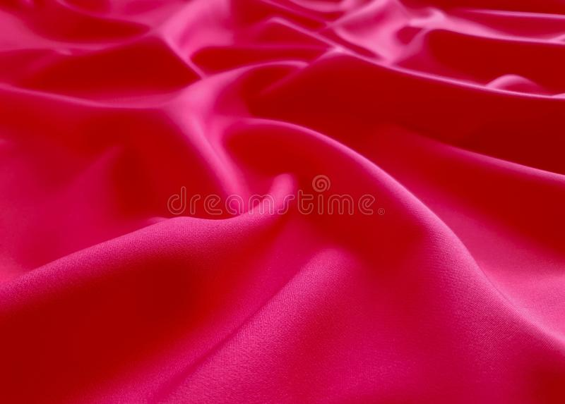 Glossy Texture, flat coral background, fabric pattern. Vivid and rich coral fabric, heavy fabric on a white background, wallpaper royalty free stock image
