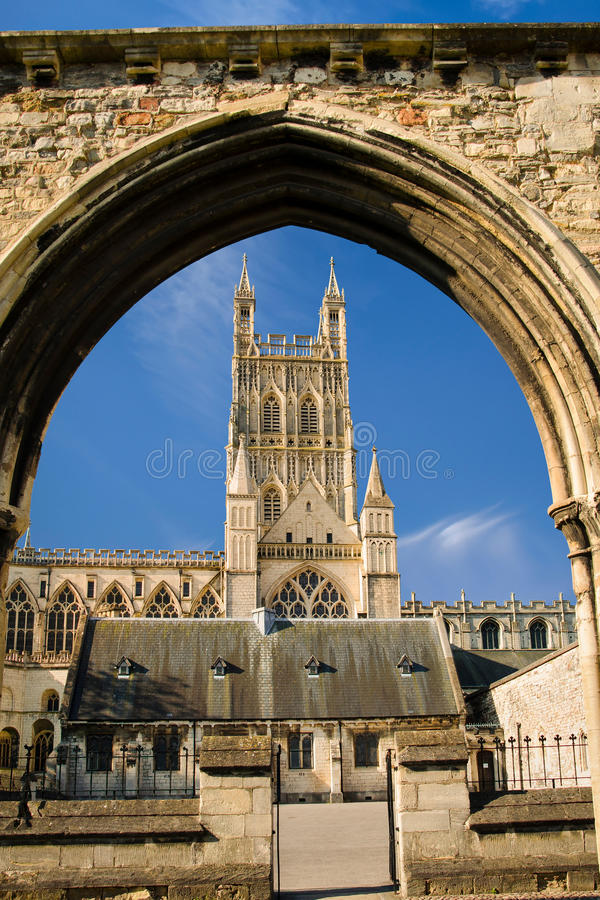 Gloucester Cathedral viewed through remains of Infirmary Arches. View of Gloucester Cathedral Church of St Peter and the Holy and Indivisible Trinity through royalty free stock image