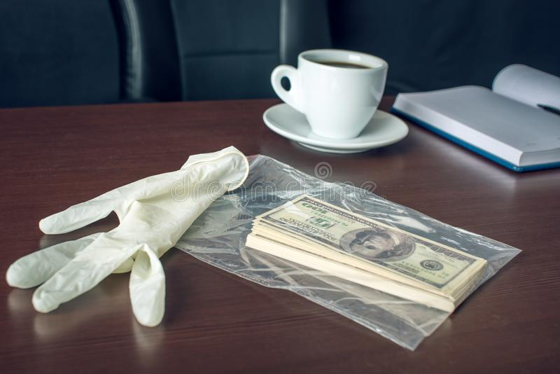 Bribe on the table in the form of dollar bills. Caught red-handed and evidence of the crime. Corruption and bribery. The glove and the bribe on the table in the royalty free stock images