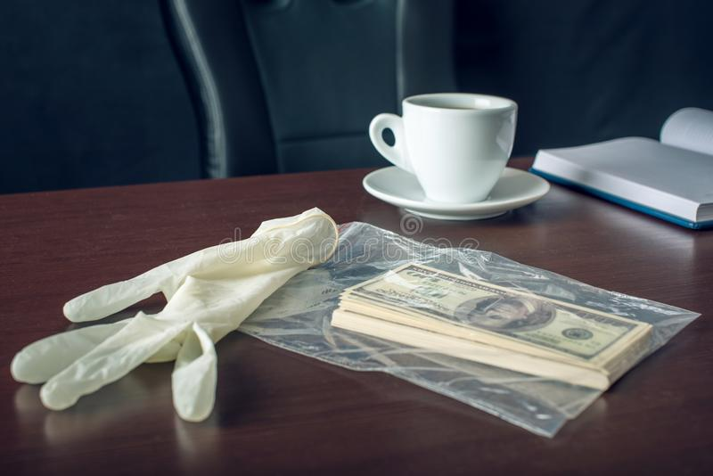 Bribe on the table in the form of dollar bills. Caught red-handed and evidence of the crime. Corruption and bribery. The glove and the bribe on the table in the stock photos