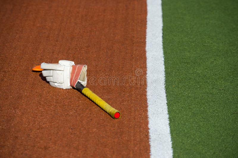 Glove with a yellow stick on brown and green grass.  stock images