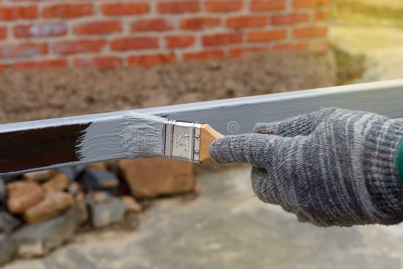 Gloved ржавчина праймера картины руки анти- на стальных поляках для конструкции стоковые изображения