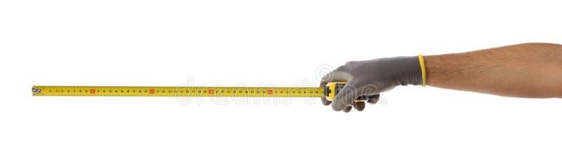Gloved рука держа ленту измерения изолированный на белой предпосылке, знамени стоковое фото