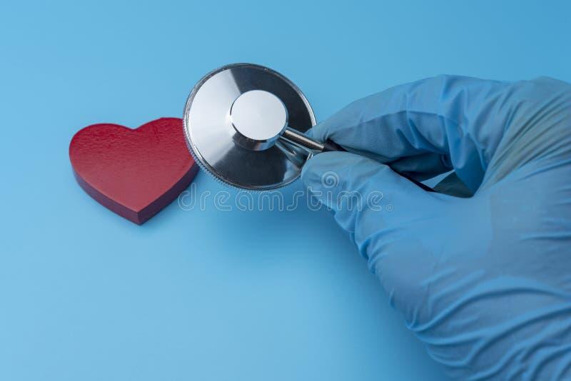Gloved рука держа стетоскоп на голубой предпосылке стоковые фотографии rf