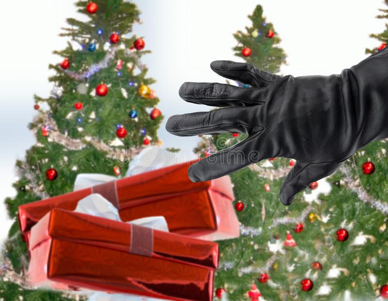 Stealing xmas gifts. Gloved black hand of a thief stealing Christmas gifts next the xmas trees stock image