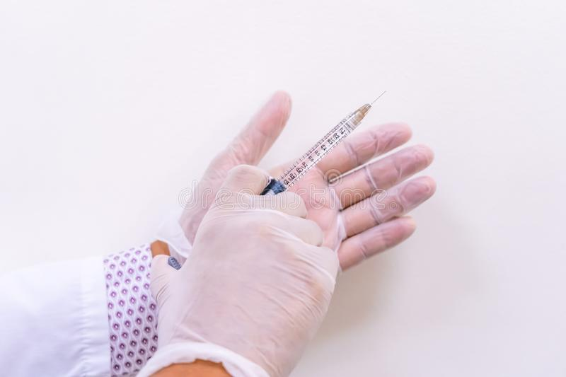 Gloved doctor hands holding an injection vial of a hyaluronic acid HA based dermal filler for anti-aging and volumizing face tre stock photo