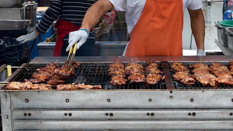 Gloved hand het draaien vlees die op grote BBQ roosteren stock foto's