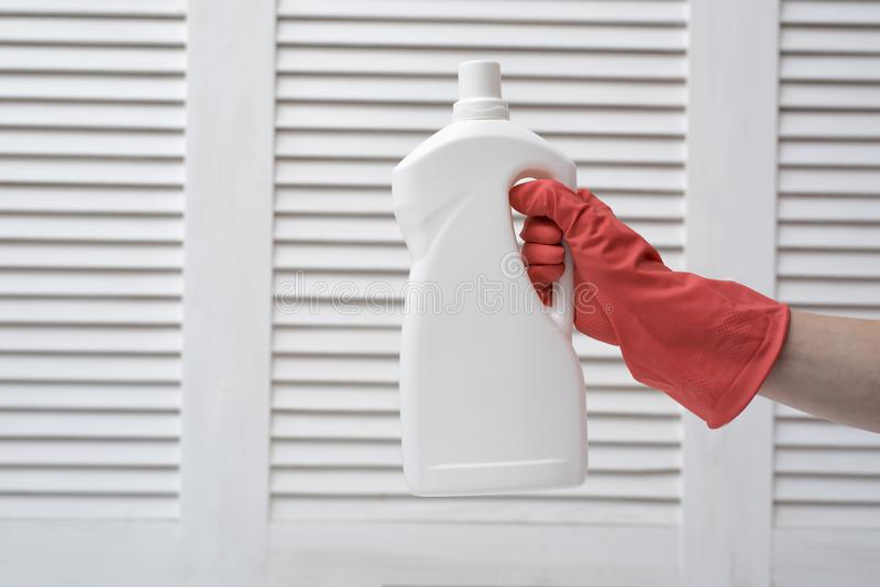 Gloved hand holding a big white bottle. Washing concept royalty free stock photos