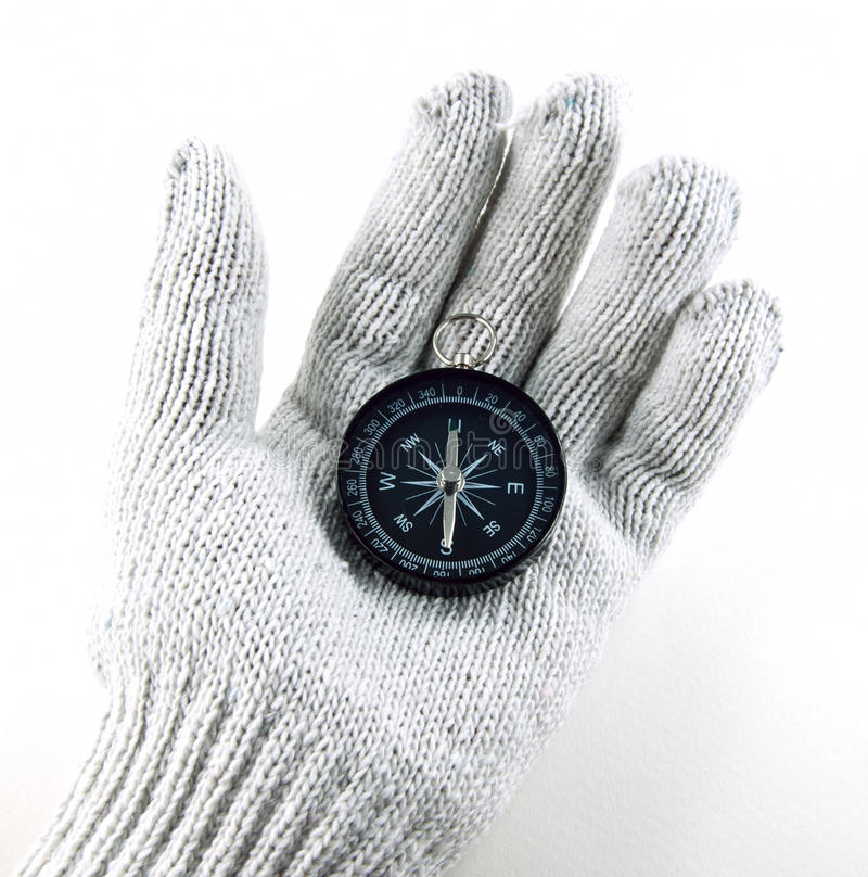 Gloved hand holding a compass. Compass on gloved hand on white background stock images