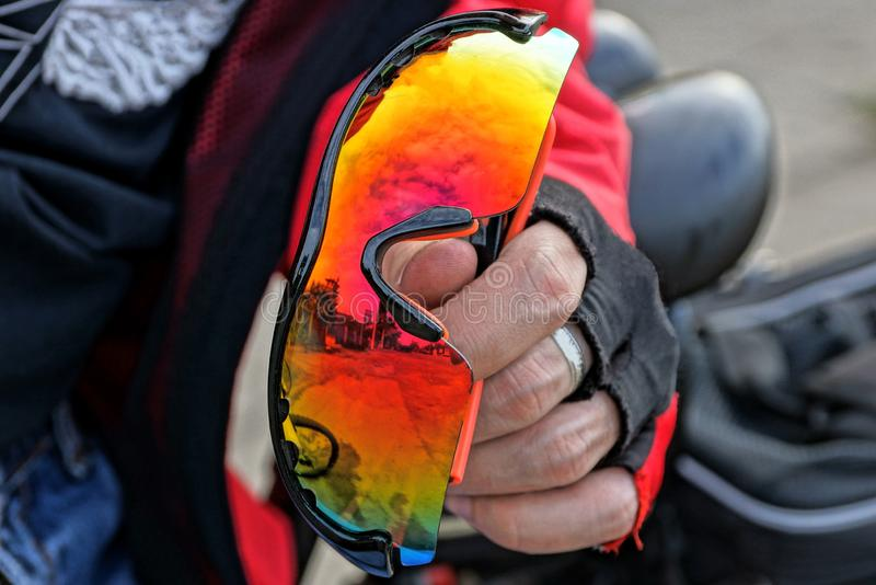 Gloved hand holds colored sport glasses stock image