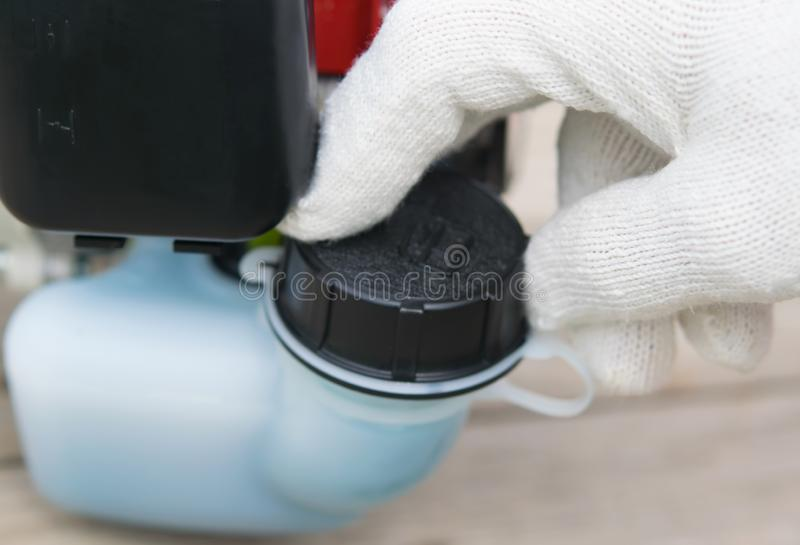 The gloved hand opens the fuel tank cap, two-stroke engine stock photography