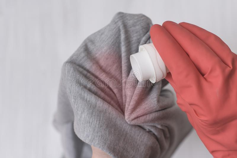 Gloved hand pouring the washing liquid onto the stain on clothes. Close up.  royalty free stock image