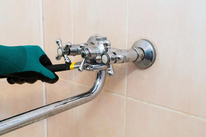 A gloved hand with a wrench repairs the faucet in the bathroom.  stock image