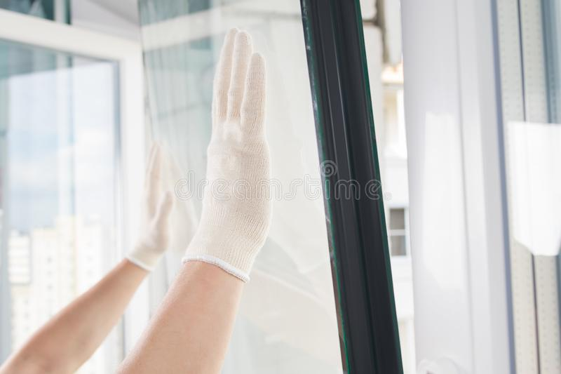 Gloved hands of a craftsman install glass in a plastic window frame stock images