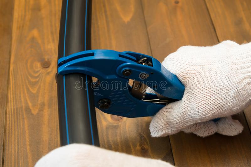 Gloved hands cut the black pipe with special scissors for cutting plastic, close-up royalty free stock photo