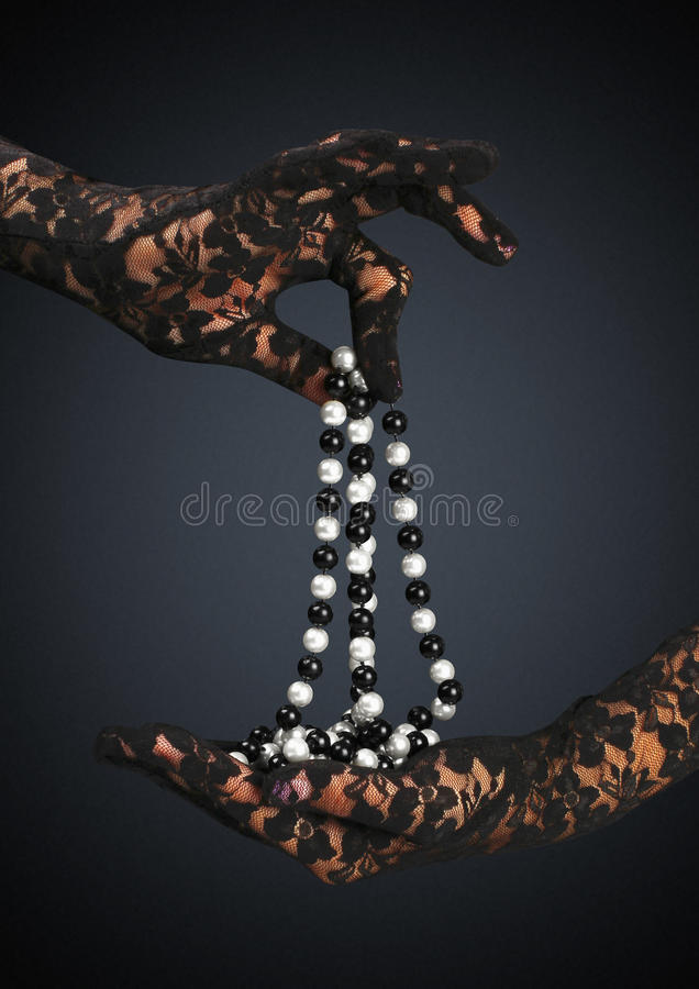Gloved hands hold jewelry necklace stock photos