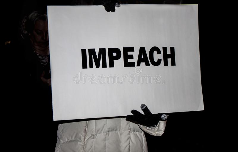 Gloved hands of person in winter coat holding IMPEACH sign at night-time rally stock image
