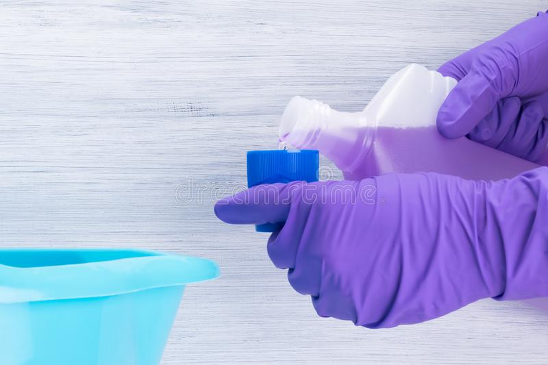 Gloved hands pouring means into dispensing cap on gray background stock photo