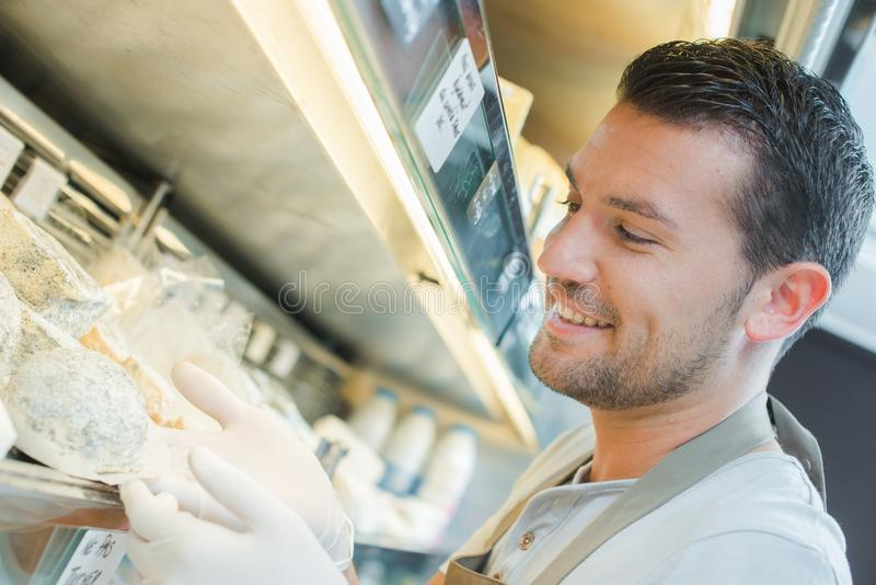 Gloved man at cold counter. Apron stock image
