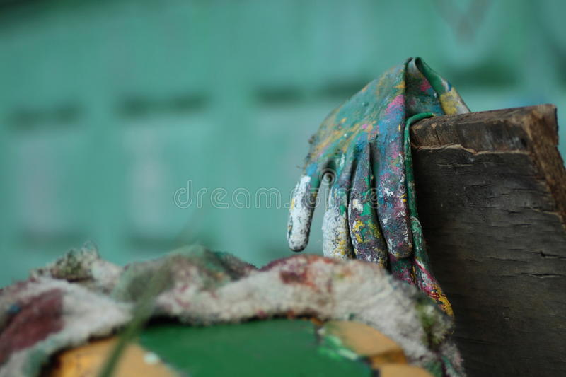 Gloves covered with paint. Working gloves covered with paint on a desk royalty free stock photography