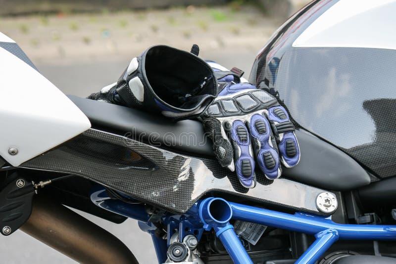 Gloves of a motor biker on a motor bike. Gloves of a motor biker lying on a motor bike during a break stock image