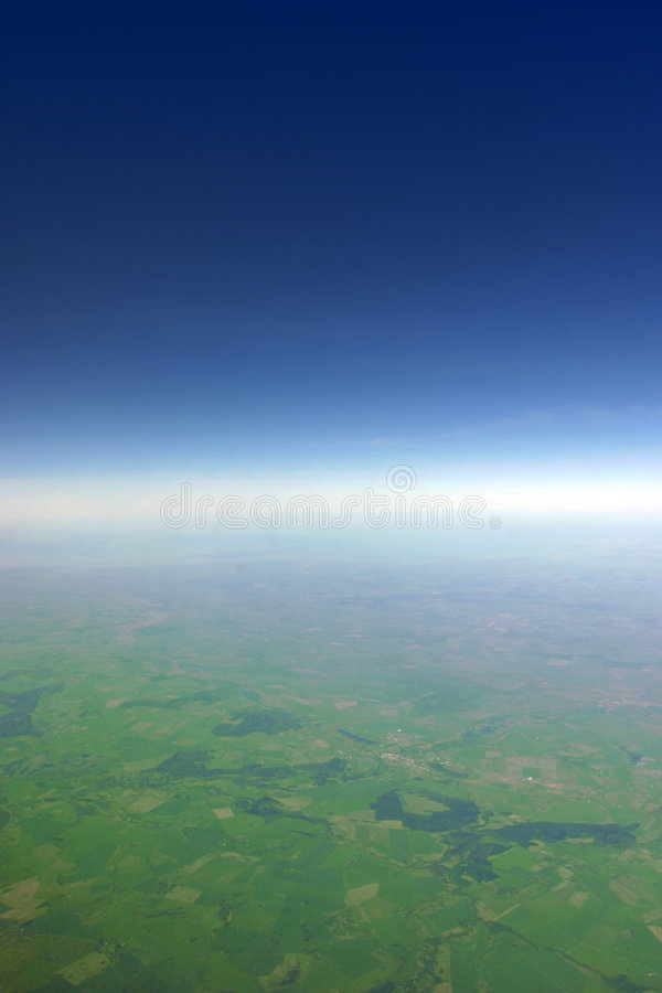 Glow horizon line. Aerial view of green fields fading away at the horizon line royalty free stock photography