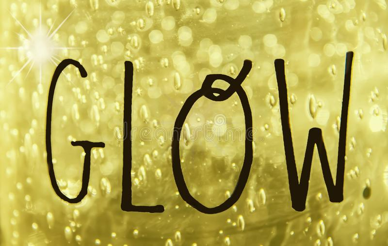 GLOW - The word glow written in freehand on golden bokeh textured background with sparkle.  vector illustration