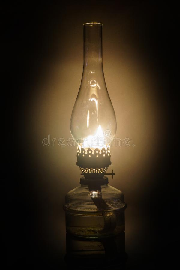 Glowing antique old kerosene oil lamp with vintage glass chimney royalty free stock images