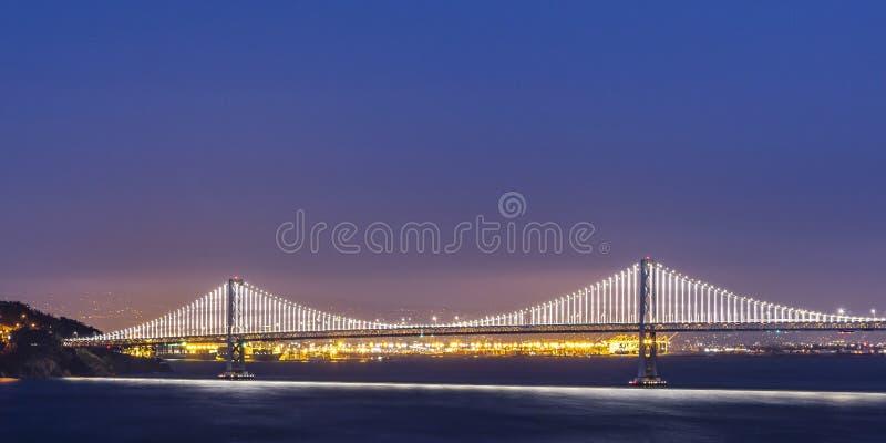 Glowing Bay Bridge over San Francisco bay at night stock photos