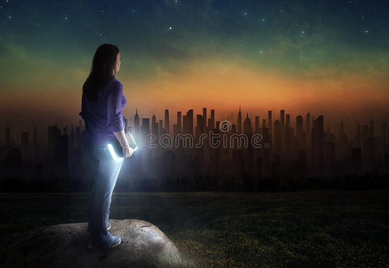 Glowing Bible and dark city stock images