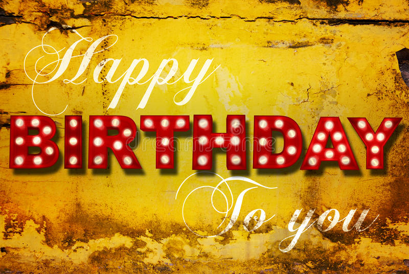 Glowing birthday greetings over distressed yellow paint royalty free stock images