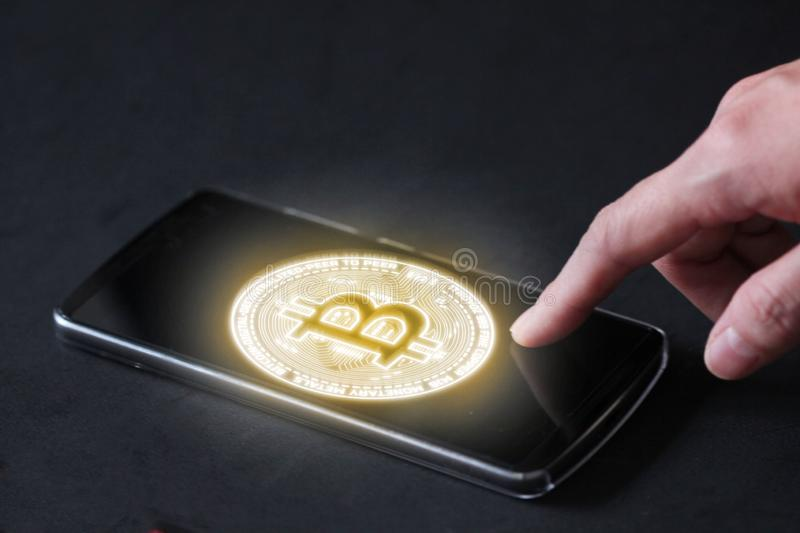 Glowing bitcoin BTC in mobile phone. Business woman use finger to touch on phone to activate payment using bitcoin royalty free stock images