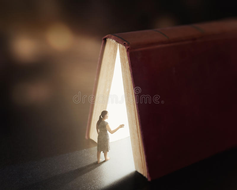 Glowing book with woman. stock image