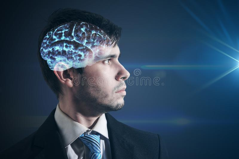 Glowing brain inside man`s head. Businessman is looking in light. stock photography