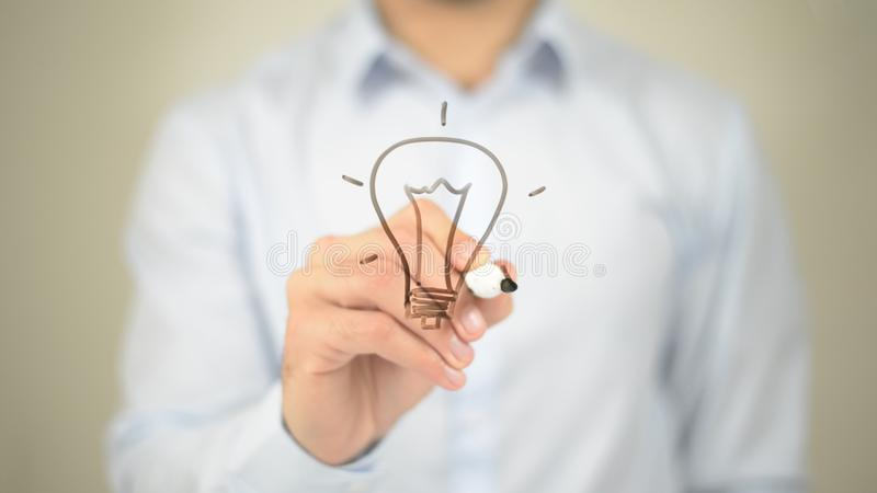 Glowing Bulb Concept, Man writing on transparent screen. High quality royalty free stock photography