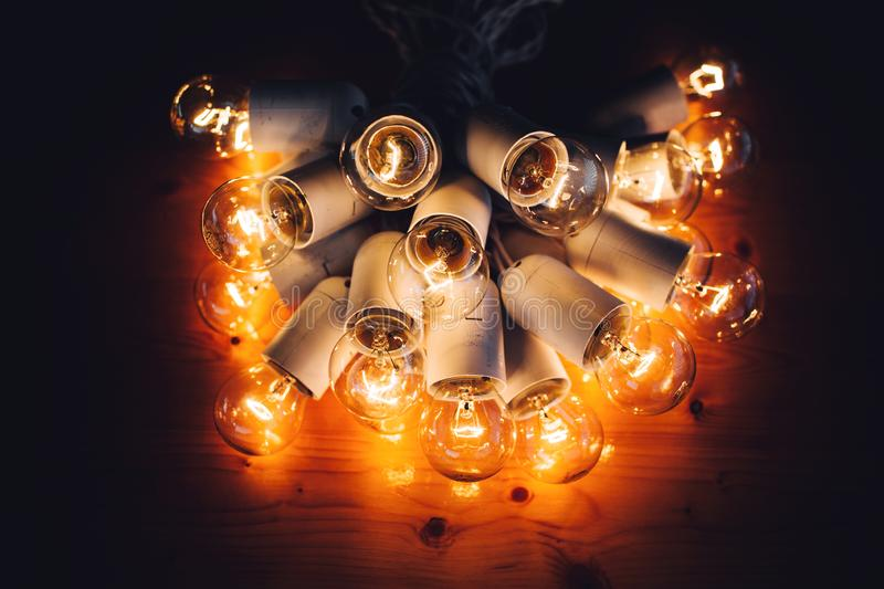 Glowing bulb uniqueness concept on brown wooden table. Glowing bulb on brown wooden table royalty free stock photos