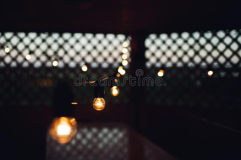 Glowing bulb uniqueness concept on brown wooden table. Glowing bulb on brown wooden table royalty free stock photo